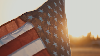 American flag blowing over a field at sunset thumbnail