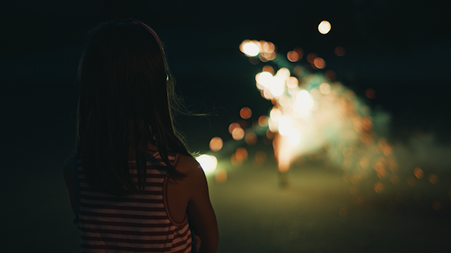 A young girl stands and watches fireworks thumbnail