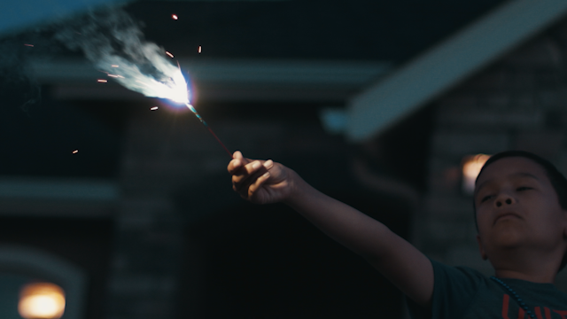 A young boy is holding a sparkler and smiling thumbnail