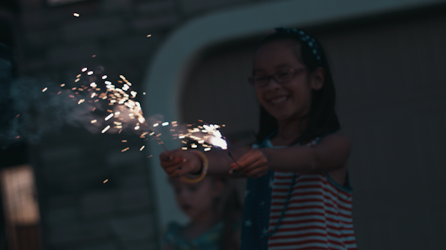 A young girl is smiling and holding sparklers thumbnail