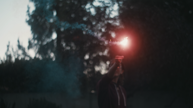 A girl is playing with a sparkler in a backyard thumbnail