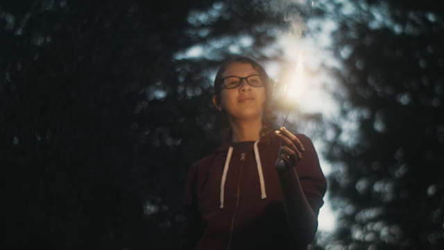 A girl looks at a sparkler she's holding thumbnail
