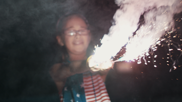 A girl holds two sparklers out in front of her thumbnail
