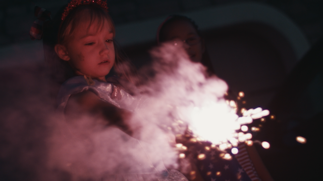 A young girl holds a red glowing sparkler thumbnail