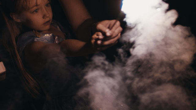 A little girl plays with a smokey sparkler thumbnail