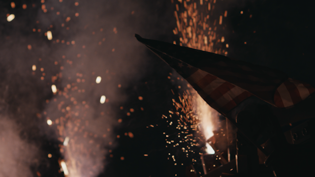 An american flag is being lit up by sparks and smoke thumbnail