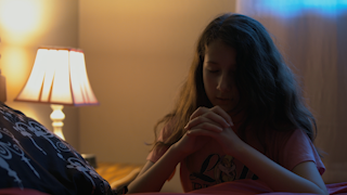 A young girl prays and her bed side before going to sleep thumbnail