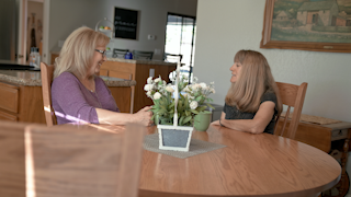 Two women are talking and laughing in a kitchen thumbnail