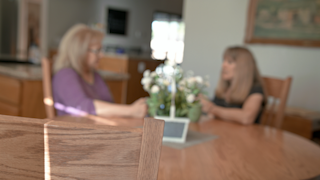 Two women are at a kitchen table talking to each other in the background thumbnail