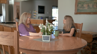 Two women are enjoying each others company at a kitchen table thumbnail