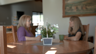 Two women are sitting at a table having a conversation thumbnail