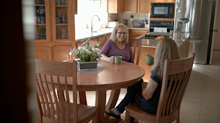 Two women are drinking coffee and talking at a kitchen table thumbnail