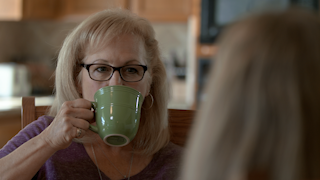 An older woman sips coffee while listening to her friend thumbnail