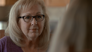 An older woman nods as she listens to her friend talk thumbnail