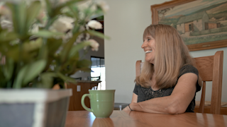 An older woman laughs and smiles while sitting at a kitchen table thumbnail