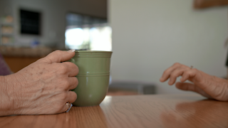 An older womans hand is holding a coffee mug on a kitchen table thumbnail
