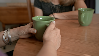 An older womans hands are holding a coffee mug at a kitchen table thumbnail