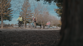 A group of cyclists ride down a bike path thumbnail