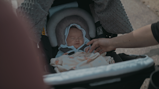 A baby sits in a stroller while her mother rubs her hand thumbnail