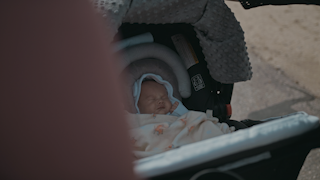 A blanket is pulled back revealing a baby in a stroller thumbnail