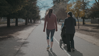 Two women walk down a pathway and talk to each other while pushing a stroller thumbnail