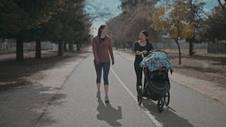 Two women walk on a pathway pushing a stroller and talking thumbnail