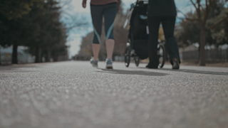 Two women walk and push a stroller down a pathway thumbnail