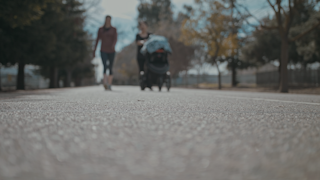 Two women walk on a pathway pushing a stroller thumbnail