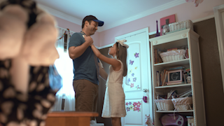 A father dances with his young daughter in her room while playing dress up thumbnail