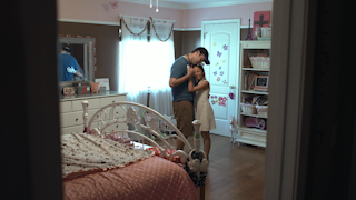 A father dances with and hugs his young daughter in her room thumbnail