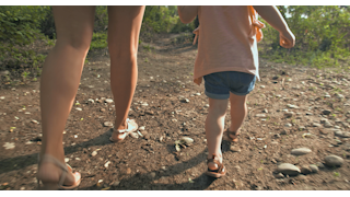 A mother walks with her young daughter out in nature thumbnail
