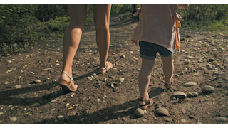 A mother walks with her young daughter on a dirt pathway thumbnail
