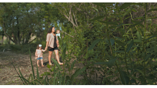 A mother walks with her children through green trees and plants thumbnail
