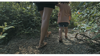 A mother holds her daughters hand and walks down a dirt path thumbnail