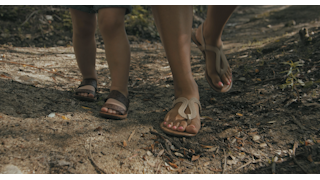 A mother and daughter's feet walking on a dirt path thumbnail