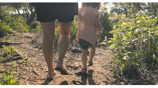 A mother walks with her young daughter down a dirt path surrounded by green plants thumbnail