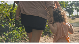 A little girl holds her mom's hand as they walk through nature thumbnail