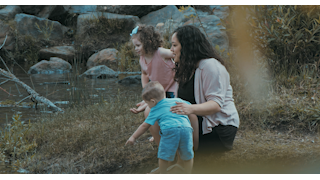 A mother plays with her children near the water thumbnail