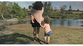 A mother and her children run to the waters edge thumbnail