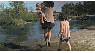 A mother and her children walk up to the waters edge thumbnail
