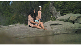 A mother sits near a pond on a rock with her children thumbnail