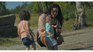 A mother plays with her children near the edge of a pond thumbnail