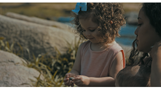 A mother hands her daughter a small rock to throw thumbnail