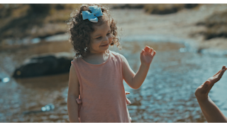 A little girl smiles and high fives her mom near a pond thumbnail