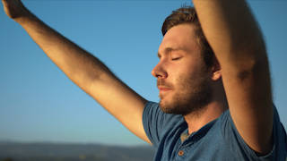 A man is raising his hands in worship at sunset thumbnail