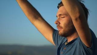 A man is raising his hands and closing his eyes in worship at sunset thumbnail