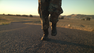 A soldier is jogging up a road at sunset thumbnail