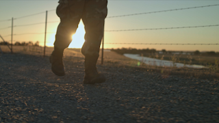 A soldier is jogging on gravel at sunset thumbnail