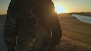 A soldier is walking down a road next to a fence at sunset thumbnail