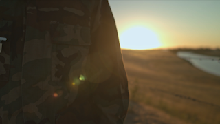 A soldier is walking along a fence at sunset thumbnail